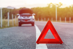 Red emergency stop sign and broken silver car on the road Stock Photography