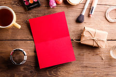 Red empty greeting card on table. Make up products. Stock Photos