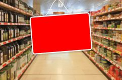 Red empty label on an abstract Supermarket background. Red blank label on a blur Supermarket background stock photo