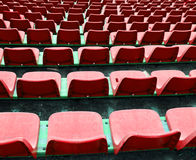Red empty small chairs on the stadium Stock Images