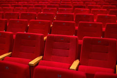 Red and empty theater seats in a row. Red and empty many theater seats in a row Royalty Free Stock Images