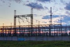 Red en la estación del transformador en la salida del sol, alto voltaje Foto de archivo