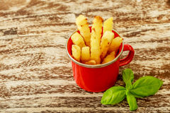 Red enameled cup with potato fries decorated with two cherry tomatoes, over wooden table. Top view. Stock Image