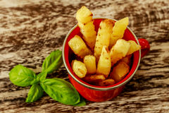 Red enameled cup with potato fries decorated with two cherry tomatoes, over wooden table. Top view. Stock Photos