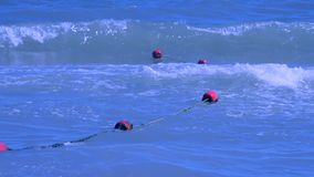 Red enclosing buoys float on waves in the sea on summer. Red old enclosing buoys with green algae float on waves in the sea on summer sunny day stock video footage