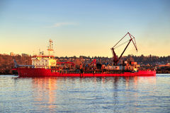 Red engineering ship on river at sunset Stock Photo