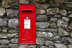 Red English letterbox. A traditional red English letterbox mounted in a dry stone wall in the village of Buttermere in the English Lake District national park Stock Photos