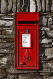 Red English letterbox. A traditional red English letterbox mounted in a dry stone wall in the village of Rydal in the English Lake District national park Royalty Free Stock Photo