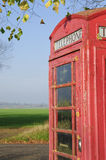 Red English phone booth in countryside Royalty Free Stock Photography