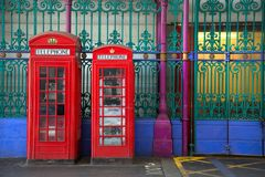 Red english phone booths with green fence. Two red booths in two different sizes with green and blue iron fence in background in Smithfield market in London UK Stock Image