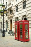 Red english phone booths in a street. Two red booths and a black lamp post in the street in London UK Stock Images