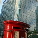 Red English postbox on architectural background. Traditional red English postbox on modern architectural background. London, UK Royalty Free Stock Photos