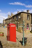 Red English Telephone Box and Terrace Houses in Haworth. Red English telephone box and terraced houses in the village of Haworth in Yorkshire, home of the Bronte Stock Images