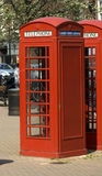 Red English Telephone boxes. In the town centre with email,text and phone sign Royalty Free Stock Photo