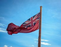 Red Ensign Flag on a Passenger Ferry in Scotland, UK. British Red Ensign Flag Against Blue Sky on a Vessel in Scotland, UK stock images