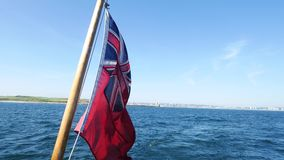 Red Ensign (UK flag) flying from a tourist pleasure boat on Aberdeen Coast, Scotland, UK stock video footage