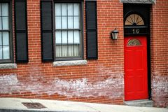Red entrance door to a brick building showing number sixteen on a street with glass windows royalty free stock image