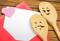 Red envelope with couple wooden spoon Royalty Free Stock Image