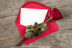 Red envelope with faded rose. Red envelope with blank letter and faded rose on wooden background stock images