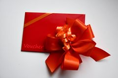 Gift voucher with red bow. Red envelope with gift voucher for birthday valentine christmas or surprise gift royalty free stock images