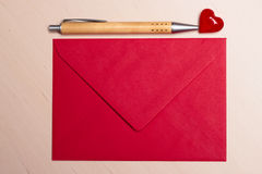 Red envelope heart and pen on table Royalty Free Stock Photos
