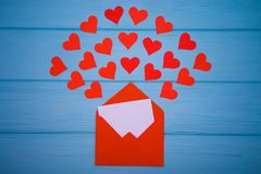 Red envelope with love letter above blue background with many hearts around Stock Images