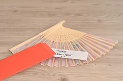 A red envelope for money for the Chinese New Year. Chinese New Year design. A red envelope for money in the Chinese New Year   with a hand fan and a note  Happy Royalty Free Stock Photo