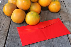 A red envelope packet or ang paw with stack of fresh oranges on old wooden board background. Chinese new year festival concept stock images