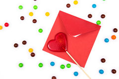 Red envelope and red lollipop in the shape of a heart on the white background with colorful button-shaped chocolates. Royalty Free Stock Images