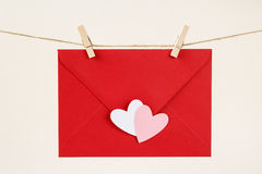 Red envelope with white and pink hearts on a rope with wooden clothespins royalty free stock photo