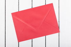 Red envelope on white wooden background Royalty Free Stock Photography
