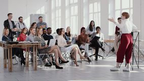RED EPIC Group of happy multiethnic business people listen to female coach speaking at modern office seminar slow motion. Team of diverse young business people stock video footage