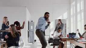 Red Epic Happy fun young black boss businessman doing epic dance at office celebrating success with team slow motion.