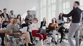 RED EPIC Happy middle aged coach businessman leads seminar discussion at modern office for multiethnic team slow motion. stock footage