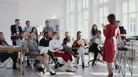 Red epic happy middle aged female coach giving speech at modern office seminar event for multiethnic team slow motion. stock footage