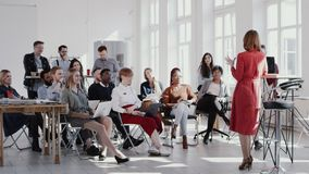 RED EPIC Happy multiethnic business people raise hands, listen to female coach at modern office seminar slow motion. stock footage
