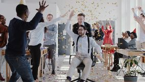 RED EPIC Happy young boss celebrates success with colleagues team and confetti at multiethnic modern office slow motion. stock footage