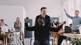 Red Epic-W Happy fun crazy young African male office worker enjoying career success at healthy office slow motion. Excited black businessman celebrating stock video