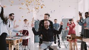 RED EPIC-W Happy middle aged boss celebrates success with team and confetti at multiethnic healthy office slow motion. Young diverse team congratulating male stock video