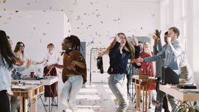 RED EPIC-W Happy young multiethnic female colleagues celebrate success with team and confetti at office slow motion. Young silly excited business women dancing stock video footage
