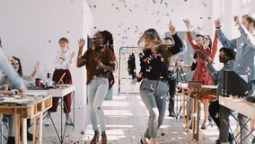 RED EPIC-W Happy young multiethnic female colleagues celebrate success with team and confetti at office slow motion.