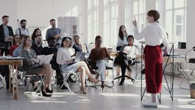 RED EPIC Young short haired business woman giving seminar talk at modern office, multiethnic team clapping slow motion. stock video