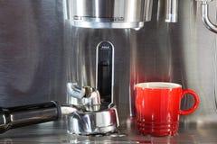 Red espresso coffee cup on mettallic espresso maker Stock Image