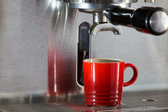 Red espresso coffee cup on mettallic espresso maker Stock Image