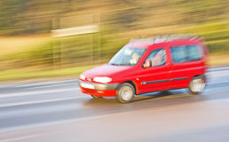 Red Estate car driving on a country road. A panned image of a red  estate car speeding along a country road Royalty Free Stock Photo