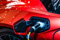 Free Red EV Car At Charging Station With The Power Cable Supply Plugged In. Power Supply Connect To Electric Vehicle For Charging The Royalty Free Stock Photos - 157283118