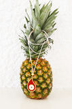 Red evil eye necklace advertisement on pineapple Royalty Free Stock Images