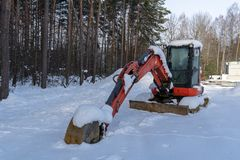A red excavator covered by snow during a cold winter day royalty free stock photos