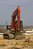 Red excavator on winter beach royalty free stock photography