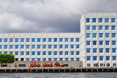 Red excursion trains ride along the waterfront along the building of the largest Danish transport campaign MERSK, Copenhagen, Denm stock image